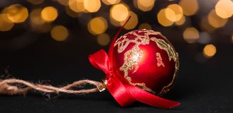 Red christmas ball on light abstract background. Christmas greeting card. Soft focus royalty free stock image