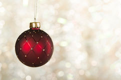 Red Christmas ball ornament. With golden trim against glowing light background royalty free stock image
