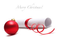 Red christmas ball and paper roll Royalty Free Stock Photo
