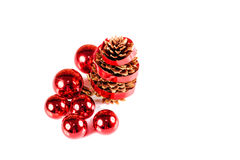 Red Christmas ball and pine cone with ribbon Stock Photos