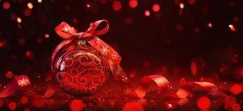 Red Christmas Ball With Reflection and Light Effects. Red Christmas Ball with Ribbon and Bow on Red Background With Reflection and Light Effects royalty free stock image