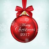 Red christmas ball with ribbon and a bow on blue background. Merry Christmas and Happy New Year 2017 Stock Photography