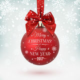 Red Christmas ball with ribbon and a bow. Red Christmas ball with ribbon and a bow, on winter background with snow and snowflakes. Merry Christmas and Happy New Stock Photo