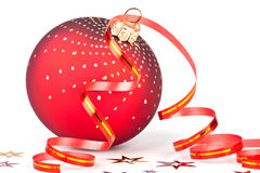 Red christmas ball with ribbon and confetti Royalty Free Stock Photography