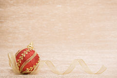 Red christmas ball with ribbon. On illuminated background Stock Images