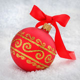 Red Christmas ball with ribbon in the snow Royalty Free Stock Photography