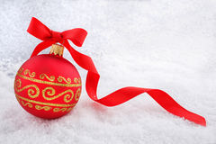 Red Christmas ball with ribbon in the snow Royalty Free Stock Photos