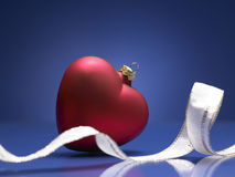 Red christmas ball in shape of heart. On a blue background Royalty Free Stock Photography