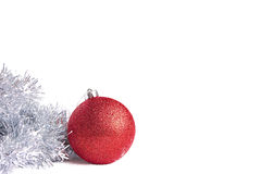 Red christmas ball with silver tinsel Royalty Free Stock Photo