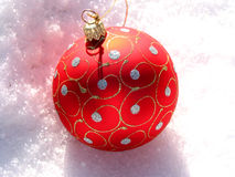 Red Christmas ball on snow. Closeup on red Christmas ball on fresh white snow Royalty Free Stock Photos