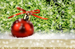 Red Christmas Ball on Snow with Christmas Tree. Stock Photo