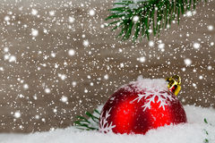 Red christmas ball with snow flakes and green branch. On wooden background Stock Images
