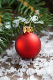 Red Christmas ball in the snow and spruce branches, close-up Royalty Free Stock Photo