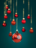 Red christmas ball with snowflakes. Closeup of hanging christmas red globe decorated with snowflakes with golden threads on blue gradient background with blurred royalty free stock photo