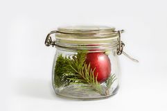 Red Christmas ball and spruce branch in a glass jar. Isolated on white royalty free stock photos