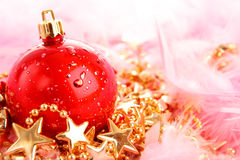 Red christmas ball on stars and pink fluff Royalty Free Stock Photos