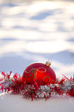 Red Christmas ball toy on fresh snow Royalty Free Stock Images
