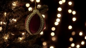 Red Christmas ball on tree on bokeh lights background.  stock footage