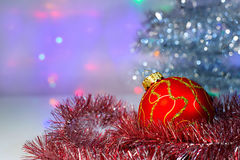 Red Christmas ball under the tree and tinsel Stock Photography