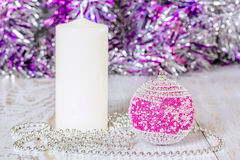 Red Christmas ball, white candle and beads Stock Photos