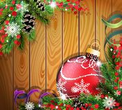 Red Christmas ball on wooden background. Red Christmas ball, cones, berries and fir tree branches on wooden background Stock Image