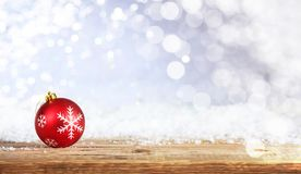 Christmas ball on a wooden desk, snowy bokeh background stock image