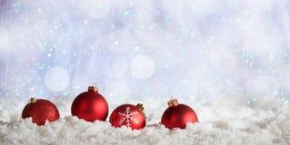 Red Christmas balls row on Christmas snowy bokeh background Stock Photos