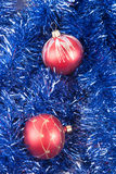 Red Christmas balls on the background of blue tinsel Stock Photos