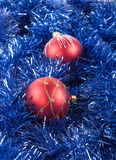 Red Christmas balls on the background of blue tinsel Royalty Free Stock Photo