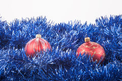 Red Christmas balls on the background of blue tinsel Royalty Free Stock Image