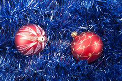 Red Christmas balls on the background of blue tinsel Royalty Free Stock Photos
