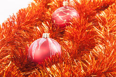 Red Christmas balls on the background of red tinsel Royalty Free Stock Photo