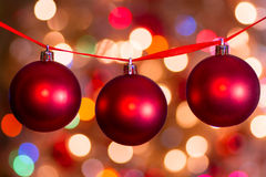 Red Christmas Balls. Red Christmas ball hanging from a red ribbon with festive light effects in the background Stock Images
