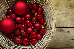 Red christmas balls and baubles in a basket on a rustic wooden t. Red christmas balls and baubles for the fir tree in a basket on a rustic wooden table, top view Royalty Free Stock Image