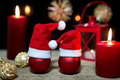 Red christmas balls, candles and a lantern on wooden table Royalty Free Stock Photos