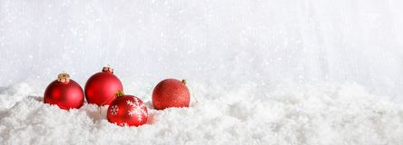 Red Christmas balls on Christmas snowy bokeh background Royalty Free Stock Photography