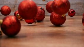 Red christmas balls falling on wooden table - slow motion stock video footage