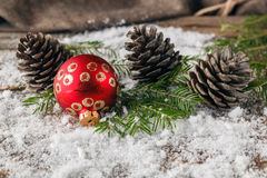Red christmas balls with fir sprigs and pine cone on snow backgr Stock Photo