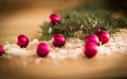 A red Christmas balls and fir-tree branches on wooden background. Royalty Free Stock Photos