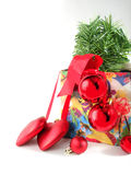 Red Christmas balls on fur-trees branch in box on white stock image