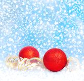 Red Christmas balls with golden streamer. On a snowy blue background Royalty Free Stock Images