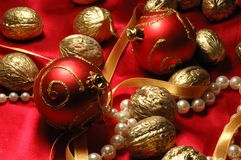 Red christmas balls and golden walnuts stock images