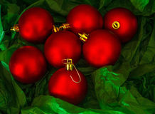 Red Christmas balls on green tissue paper Royalty Free Stock Images
