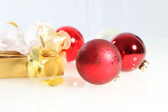 Red Christmas balls and a luxury gift Royalty Free Stock Photography