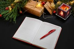 Red Christmas balls and notebook lying near green spruce branch on black background top view. Space for text Royalty Free Stock Photo