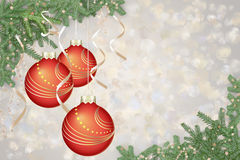 Red Christmas balls over silver background. Christmas background with red baubles and fir tree branches. Shiny silver bokeh in the background Stock Photo