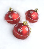 Red Christmas balls with painted snowflakes lying in the snow Royalty Free Stock Photography