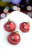 Red Christmas balls with painted snowflakes lying in snowdrift Royalty Free Stock Images