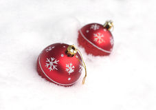 Red Christmas balls with painted snowflakes lying on white snow Stock Images