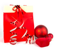 Red christmas balls and paper present bag on white Stock Photo